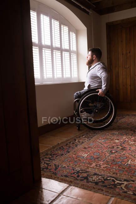 Homme handicapé en fauteuil roulant regardant par la fenêtre à la maison — Photo de stock