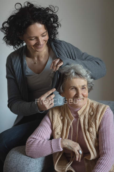 Daughter combing hair of her mother in living room at home — Stock Photo