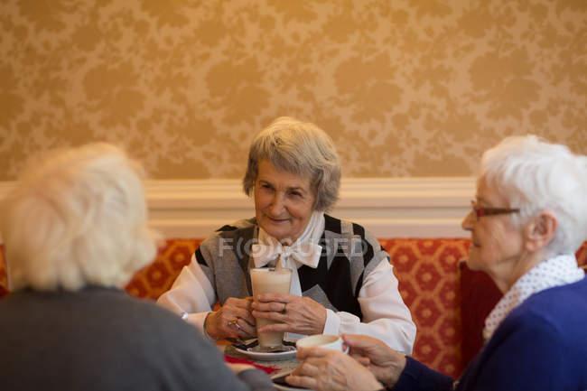 Старших друзей, имея молочный коктейль в домашних условиях — стоковое фото