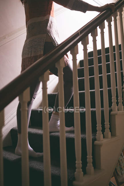 Low section of woman walking upstairs at home — Stock Photo