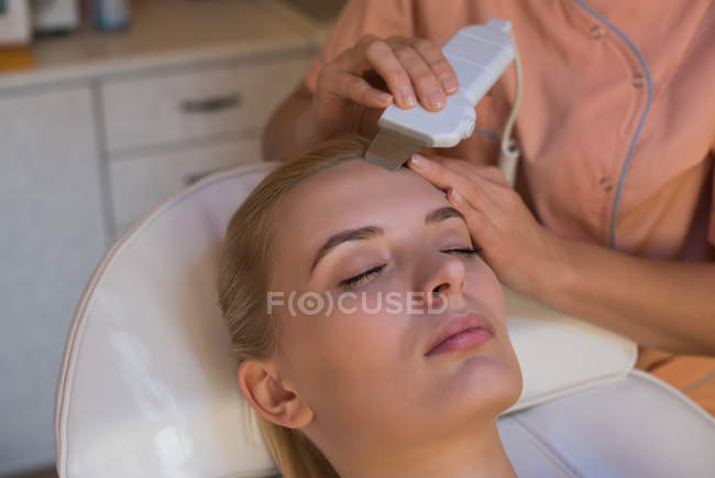 Estetista utilizzando lavasciuga ultrasuoni su cliente femminile in salotto — Foto stock