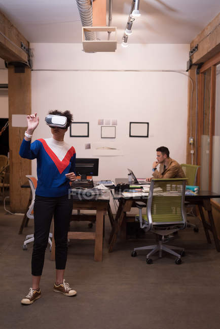 Female executive using virtual reality headset in office — Stock Photo