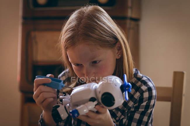 Aufmerksame Mädchen reparieren das Roboterspielzeug zu Hause — Stockfoto