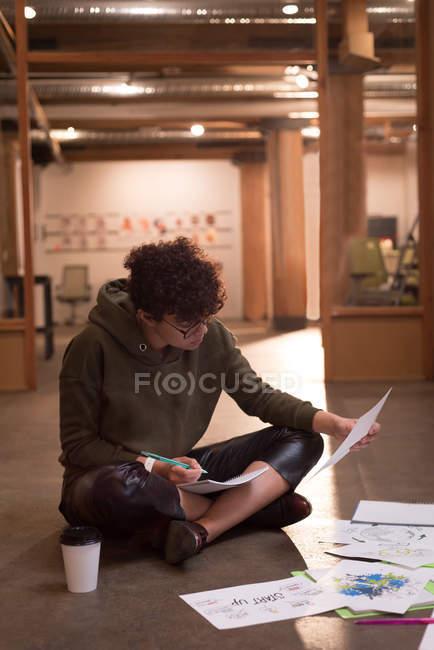 Jeune cadre femme écrivant sur le bloc-notes dans le Bureau — Photo de stock