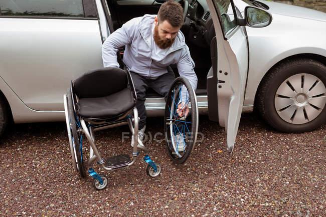 Jovem deficiente segurando cadeira de rodas enquanto embarca em seu carro — Fotografia de Stock
