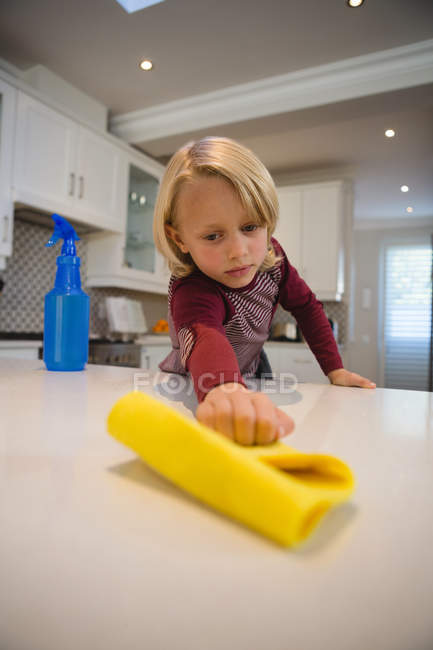 Boy cleaning kitchen worktop with rag at home — Stock Photo