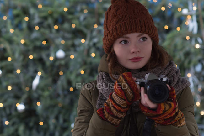 Beautiful woman in winter clothing holding vintage camera — Stock Photo