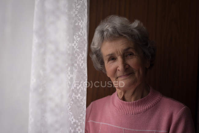 Portrait of senior woman standing near window at home — Stock Photo