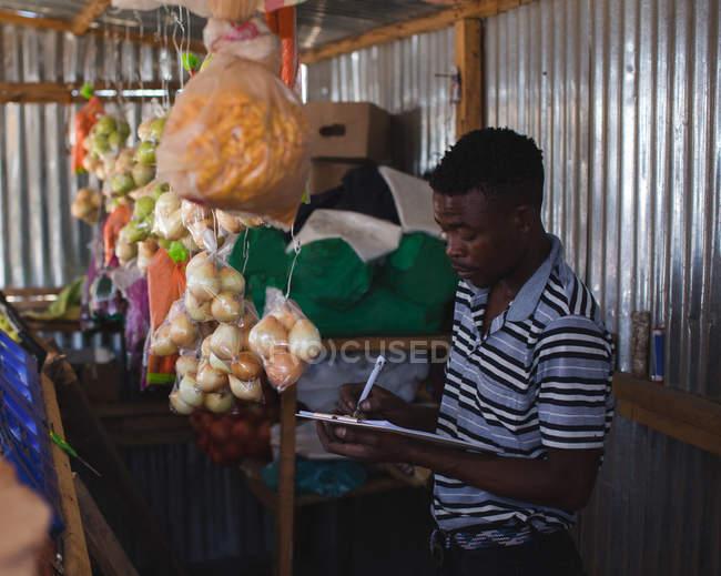 Hombre escribiendo en portapapeles en tienda - foto de stock