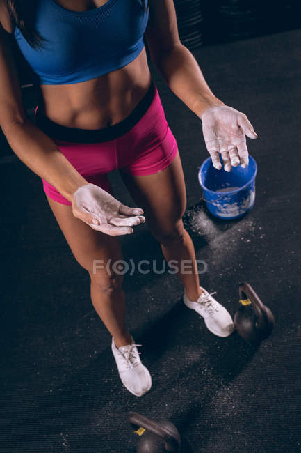 Fit woman standing with chalk powder in her hands in the gym — Stock Photo