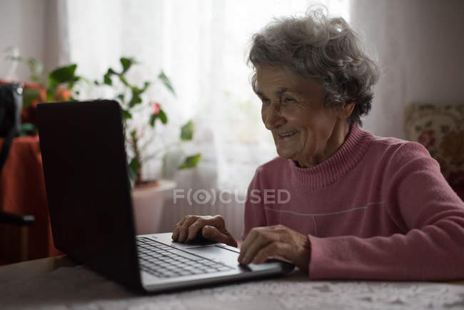 Active senior woman using laptop at home — Stock Photo