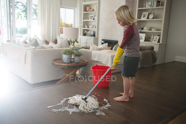Boy washing the floor with mop in living room at home — Stock Photo