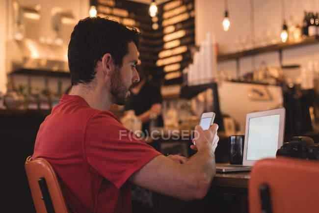 Giovane uomo utilizzando il telefono cellulare in café — Foto stock