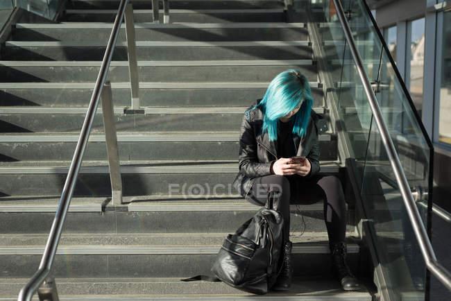 Stilvolle Frau benutzt Handy auf Treppe — Stockfoto