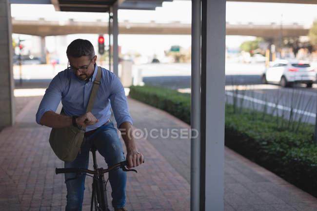 Человек смотрит на умные часы во время езды на велосипеде по тротуару — стоковое фото