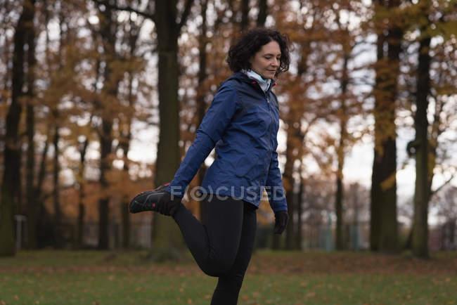 Jovem realizando exercícios de alongamento no parque — Fotografia de Stock