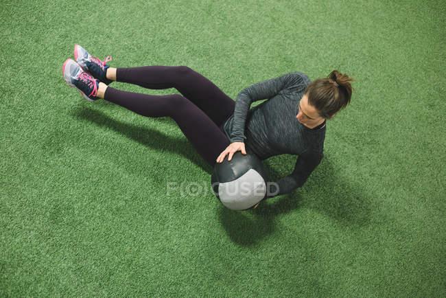 Frau, üben, dehnen mit einem Ball auf Rasen — Stockfoto