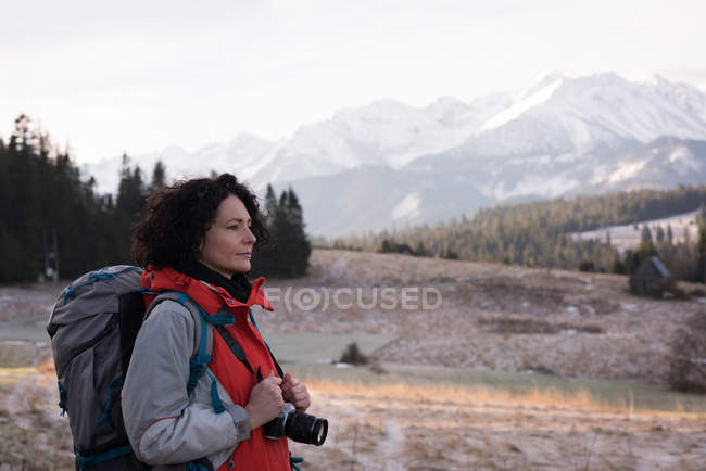 Thoughtful woman standing with backpack and digital camera during winter — Stock Photo