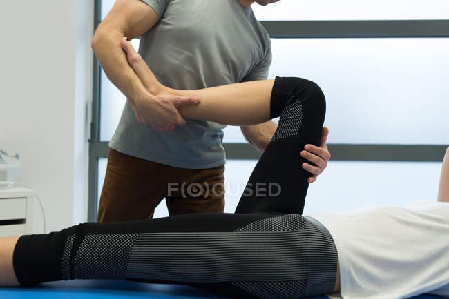 Фізіотерапевт даючи ногу масаж до жінки в клініці — стокове фото
