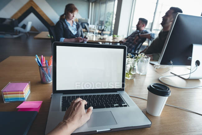Businessman using laptop while colleagues having discussion in office — Stock Photo