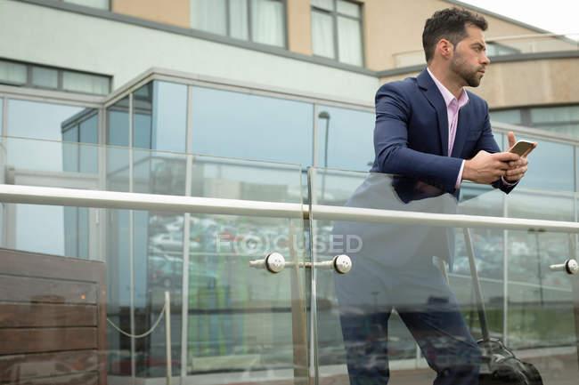 Nachdenklicher Geschäftsmann lehnt an Glasgeländer — Stockfoto
