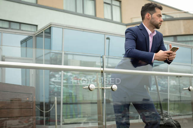 Продуманий бізнесмен, спершись на перила скла — стокове фото
