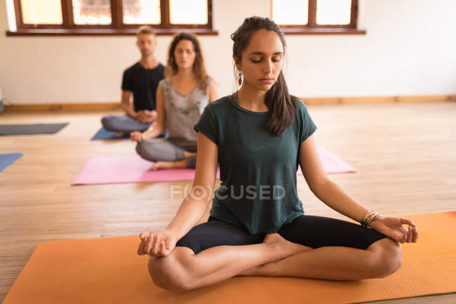 Group of people meditating together in fitness club — Stock Photo