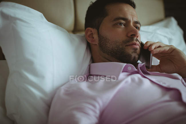 Businessman talking on mobile phone in hotel room — Stock Photo