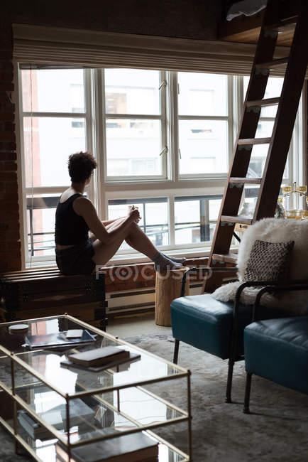 Привлекательная женщина смотрит через окно на дом — стоковое фото