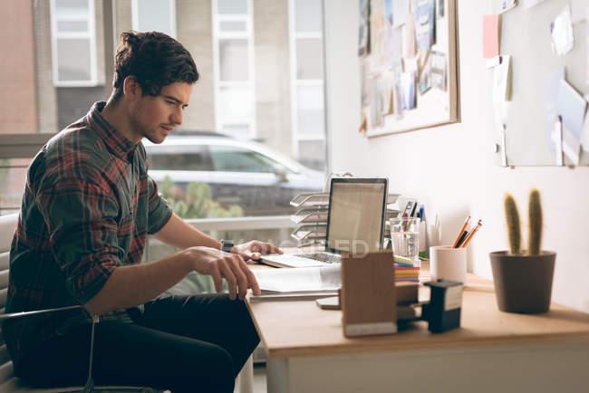 Executivo, verificando o documento na mesa no escritório — Fotografia de Stock