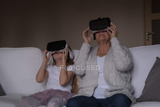 Бабуся і внучка, використовуючи віртуальну реальність гарнітуру на дому — стокове фото