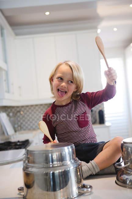 Menino brincando com utensílios na cozinha em casa — Fotografia de Stock