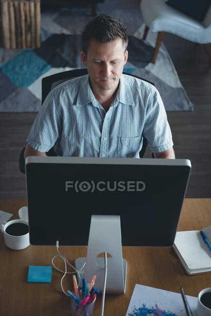 Бизнесмен, работающий за компьютером на рабочем столе в офисе — стоковое фото