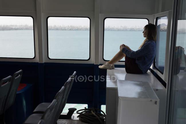 Thoughtful woman sitting near window in cruise ship — Stock Photo
