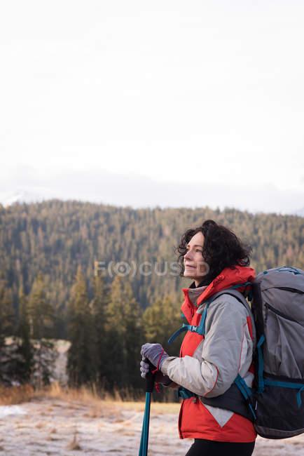 Задумчивая женщина, стоящая с рюкзаком и походным столбом зимой — стоковое фото