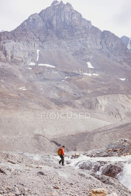 Male hiker with backpack walking alone towards river — Stock Photo