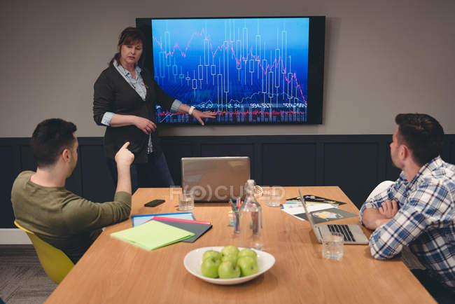 Empresária dando apresentação aos colegas na sala na sala de reuniões — Fotografia de Stock