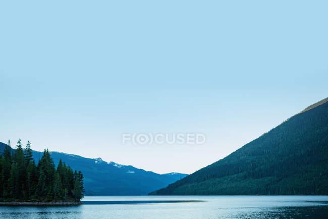 Montanha verde com lago e céu azul em um dia ensolarado — Fotografia de Stock