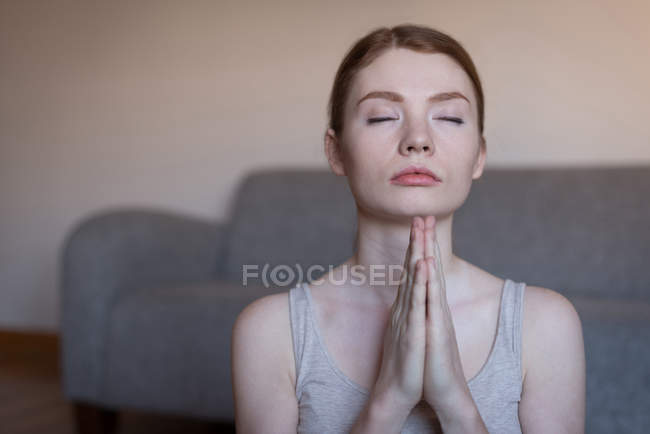 Young woman meditating with joined hands in living room — Stock Photo
