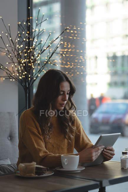 Giovane donna che utilizza tablet digitale nel ristorante — Foto stock