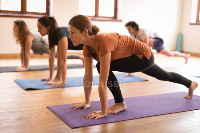 Group of people performing yoga exercise together in fitness club — Stock Photo