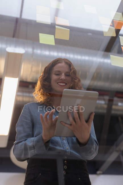 Esecutivo femminile ad angolo basso con tablet digitale in ufficio — Foto stock