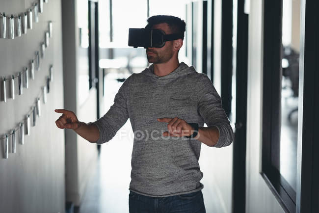 Businessman using virtual reality headset in corridor at office — Stock Photo