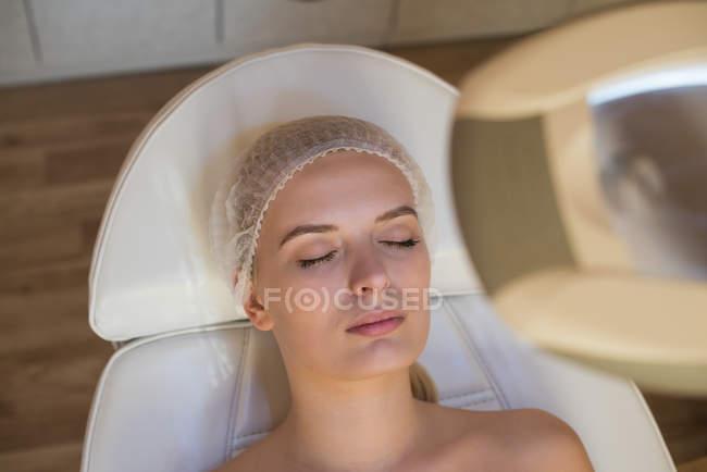 Donna ottenere trattamenti di bellezza mentre sdraiato sul letto salone in salotto — Foto stock