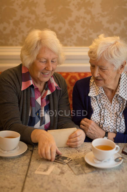 Senior friends interacting with each other while having coffee at home — Stock Photo