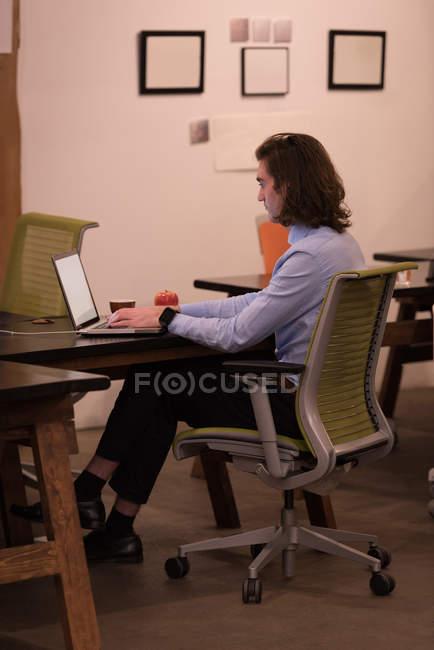 Молодой мужчина использует ноутбук в офисе — стоковое фото