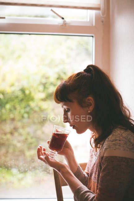 Vista laterale della donna che prende un tè a casa — Foto stock