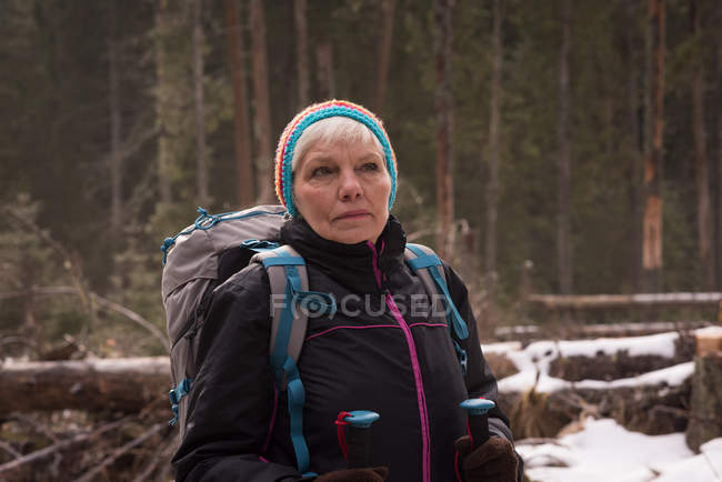 Thoughtful senior woman standing with backpack and hiking pole during winter — Stock Photo