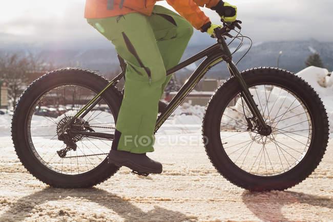 Homme monté sur sa bicyclette sur le trottoir pendant l'hiver — Photo de stock