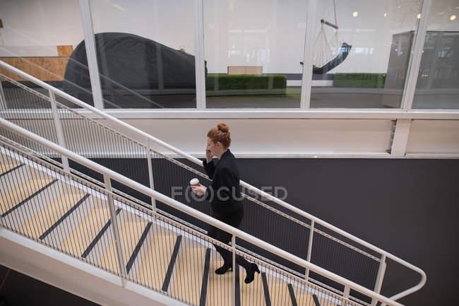 Progettista grafico femminile usando il cellulare in ufficio — Foto stock